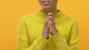 Señora joven sonriente en suéter amarillo que cuenta con las manos que se unen a, gesto que espera almacen de video