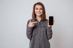 Señora joven sonriente que muestra la exhibición del teléfono móvil a la cámara Foto de archivo libre de regalías