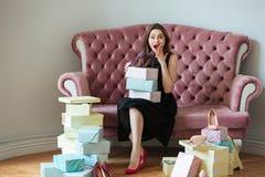 Señora joven sonriente que se sienta en el sofá dentro que elige los zapatos Imágenes de archivo libres de regalías