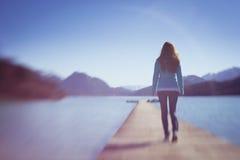 Señora joven Walking en la pequeña trayectoria de madera del espacio Imagenes de archivo