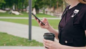 Señora joven Walking y usar del pelirrojo un teléfono en ciudad foto de archivo libre de regalías