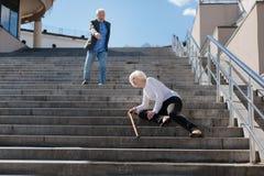 Señora jubilada que miente en las escaleras al aire libre Imagen de archivo libre de regalías