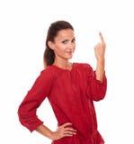 Señora latina preciosa que señala encima de su finger Foto de archivo libre de regalías
