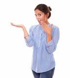 Señora latina sorprendida que detiene su palma derecha Fotografía de archivo libre de regalías