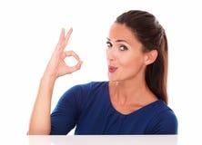 Señora linda en la camiseta azul que hace una muestra aceptable Foto de archivo