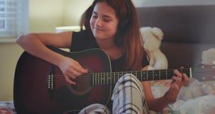 Señora linda que la juega en una guitarra en su dormitorio feliz que disfruta del tiempo, después de que la escuela tenga una rot almacen de video