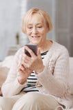 Señora lista encantada que usa su artilugio Imágenes de archivo libres de regalías