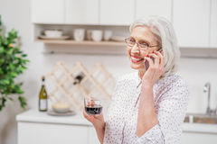 Señora madura alegre que bebe la bebida caliente en cocina Foto de archivo libre de regalías