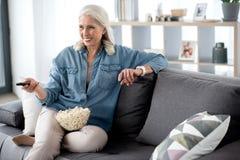 Señora madura alegre que entretiene con la televisión en sala de estar Fotografía de archivo