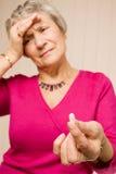 Señora madura con la tablilla o la píldora de la explotación agrícola del dolor de cabeza Foto de archivo