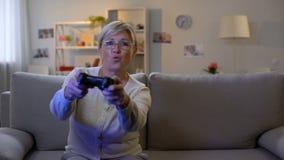 Señora madura feliz que presiona los botones de la consola que juegan el sofá casero que se sienta del videojuego almacen de metraje de vídeo