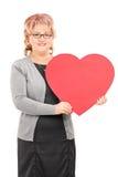 Señora madura que celebra una presentación roja grande del corazón Imagen de archivo