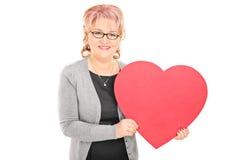 Señora madura que lleva a cabo un corazón rojo grande Foto de archivo