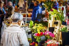 Señora madura que mira las flores el mercado semanal imagen de archivo libre de regalías