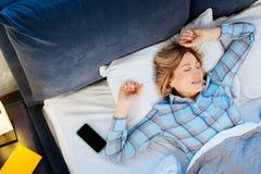 Señora madura soñolienta que miente en la almohada grande y que despierta lentamente imágenes de archivo libres de regalías