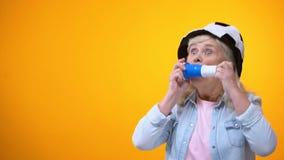 Señora mayor alegre en el cuerno que sopla del sombrero del fanático del fútbol, deporte apostando, vida activa metrajes