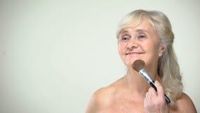 Señora mayor alegre que aplica el polvo, actitud positiva para envejecer, cuidado de la belleza metrajes