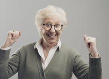 Señora mayor alegre que celebra su victoria con los puños aumentados imágenes de archivo libres de regalías
