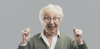 Señora mayor alegre que celebra su victoria con los puños aumentados fotos de archivo