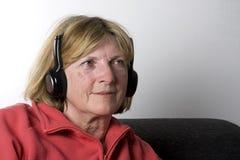 Señora mayor - auriculares Foto de archivo libre de regalías