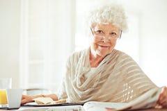 Señora mayor con el periódico de mañana Imagen de archivo libre de regalías