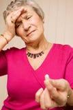 Señora mayor con la tablilla o la píldora de la explotación agrícola del dolor de cabeza Foto de archivo libre de regalías