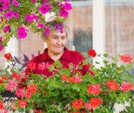 Señora mayor con las flores imágenes de archivo libres de regalías