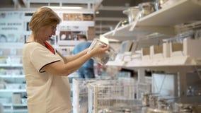 Señora mayor con los vidrios que examinan la cacerola del metal en una tienda con vajilla almacen de metraje de vídeo