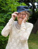 Señora mayor de risa que lleva un sombrero Fotos de archivo