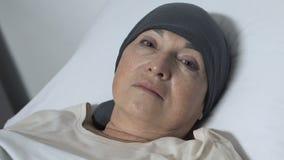 Señora mayor del trastorno en la bufanda que miente en cama y que mira la cámara, paciente de la quimioterapia almacen de metraje de vídeo