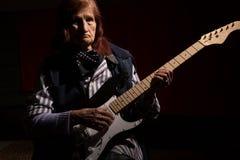 Señora mayor divertida que toca la guitarra eléctrica Fotos de archivo