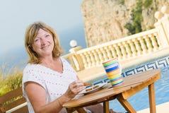 Señora mayor Eating Her Breakfast Poolside fotografía de archivo libre de regalías