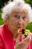 Señora mayor Eating A Waffle Imagenes de archivo