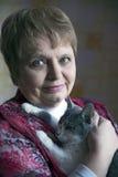 Señora mayor elegante hermosa con un gato en casa Imagen de archivo libre de regalías