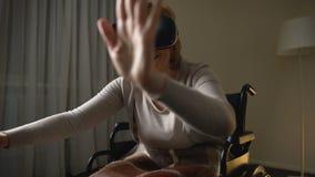 Señora mayor emocionada en la silla de ruedas que se divierte en auriculares modernas de la realidad virtual almacen de metraje de vídeo