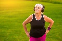 Señora mayor en auriculares Imagen de archivo