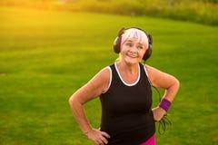 Señora mayor en auriculares Imagenes de archivo