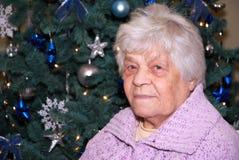 Señora mayor en el árbol de navidad Fotos de archivo libres de regalías