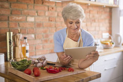 Señora mayor en la cocina Fotos de archivo