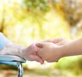 Señora mayor en la silla de rueda que lleva a cabo las manos con el vigilante joven Imagen de archivo libre de regalías