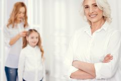 Señora mayor encantadora que presenta con la hija y la nieta que se visten detrás Fotografía de archivo libre de regalías