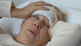 Señora mayor enferma que lleva a cabo la cabeza con la toalla mojada en la frente, sufriendo de fiebre almacen de video