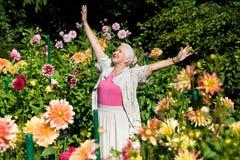 Señora mayor feliz en el jardín Imagen de archivo libre de regalías