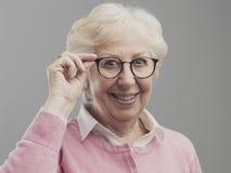 Señora mayor feliz que presenta y que muestra sus vidrios foto de archivo