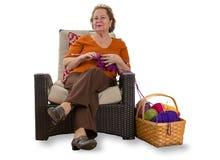 Señora mayor feliz que se relaja en una silla de mimbre Foto de archivo libre de regalías