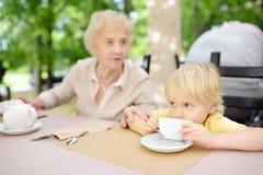 Señora mayor hermosa con su té de consumición del pequeño nieto en café o restaurante del aire libre Forma de vida mayor de la se imagenes de archivo