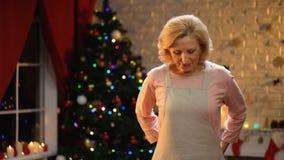 Señora mayor hermosa que pone el delantal, preparación para la celebración de Navidad de la familia metrajes