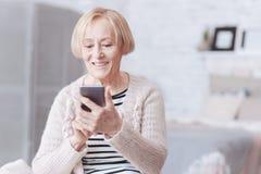Señora mayor importada positiva que mira la pantalla de su smartphone foto de archivo libre de regalías
