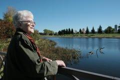 Señora mayor que disfruta de la opinión del lago Foto de archivo