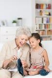 Señora mayor que enseña a su nieta a hacer punto Imágenes de archivo libres de regalías